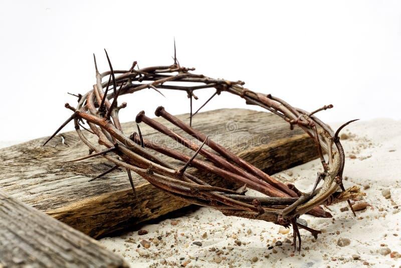 耶稣冠刺和钉子和十字架在沙子 减速火箭的样式葡萄酒 库存照片