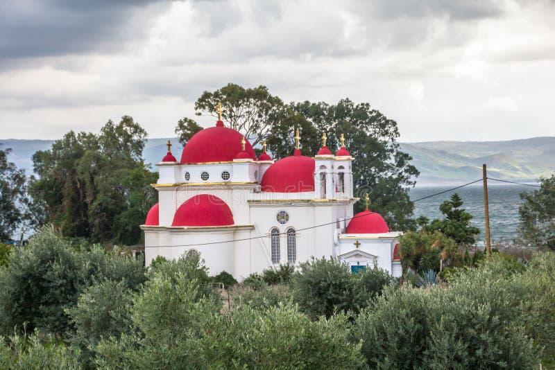 耶稣十二门徒的红半球形的希腊东正教在加利利海附近,以色列的岸的迦百农的 免版税库存照片