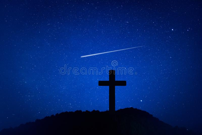 耶稣受难象十字架剪影在山的在夜间有星和空间背景 库存图片