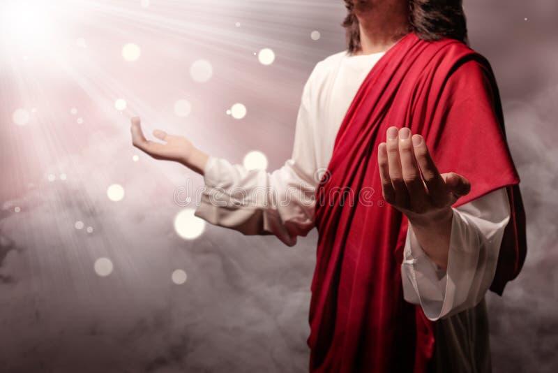 耶稣基督培养了手和祈祷给有光芒的神 免版税库存图片