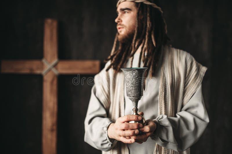 耶稣基督拿着一个杯子酒 库存照片
