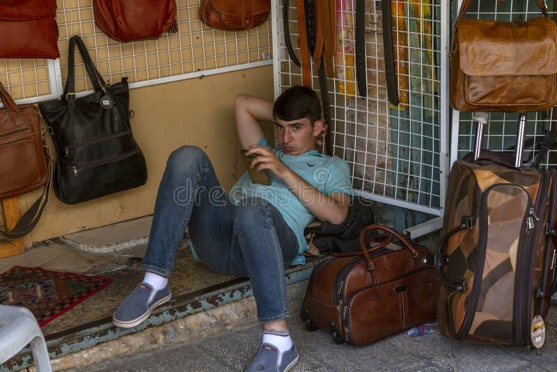 耶路撒冷,以色列,09/11/2016:卖主男孩在市场上是休息,说谎在与电话的地面上 库存图片