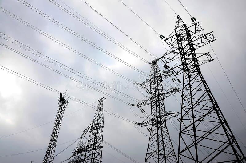 耸立输电线反对多云天空背景 电 免版税库存照片