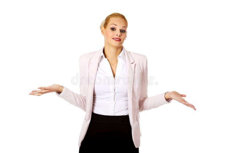 耸肩与我的年轻女商人不认识姿态 免版税库存照片