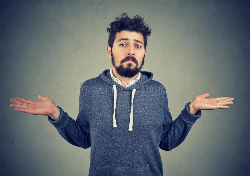耸肩的一个年轻人的画象感到无知 免版税库存照片