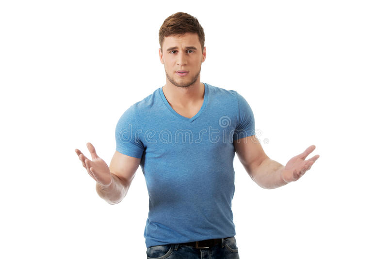 耸肩他的手的年轻人 免版税库存照片