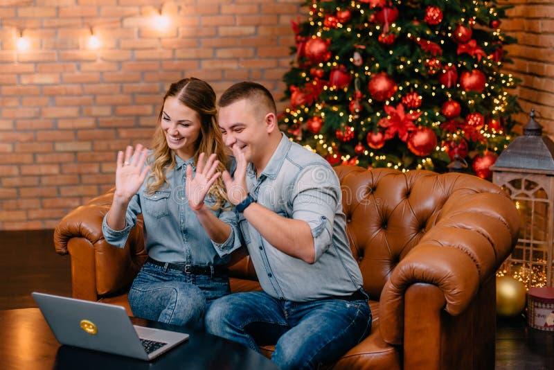 聊天与亲戚的年轻夫妇通过网络摄影 库存图片