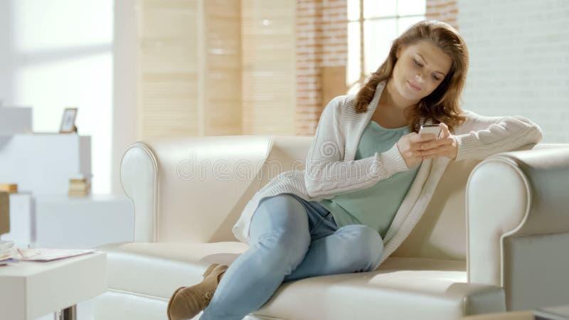 聊天与人脉的男朋友的愉快的年轻女性在手机 库存照片