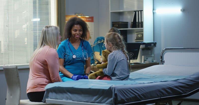 聊天与女孩和母亲的友好的医生 免版税库存照片
