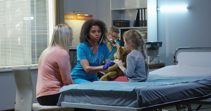 聊天与女孩和母亲的友好的医生 库存照片