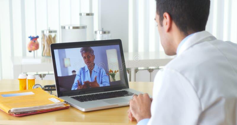 聊天与成熟患者的墨西哥医生录影 库存照片