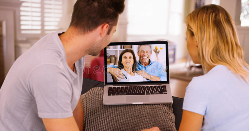 聊天与他们的膝上型计算机的父母的千福年的夫妇录影 图库摄影