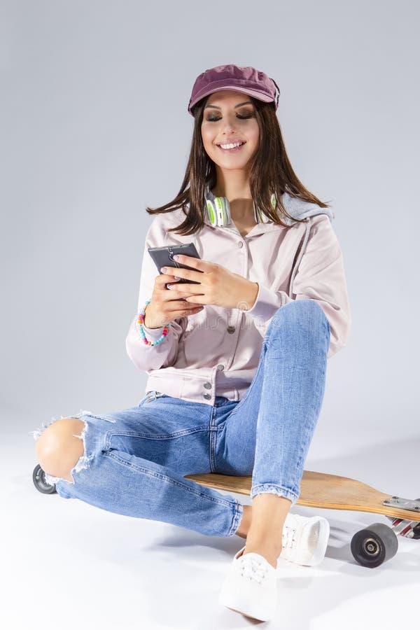 聊天使用智能手机的女孩 摆在与滑板 免版税库存图片