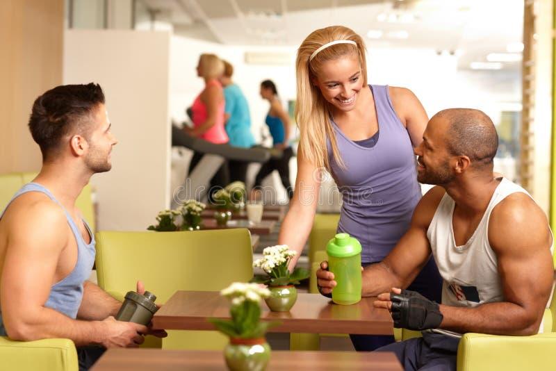 聊天在健身房酒吧的青年人 免版税库存照片