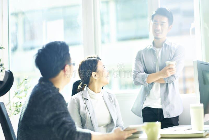 聊天在办公室的三个年轻亚裔商人 免版税库存图片