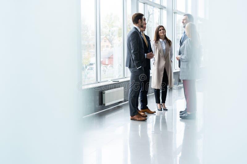 聊天在咖啡休息期间的小组现代商人站立在办公楼被日光照射了玻璃大厅里  免版税图库摄影