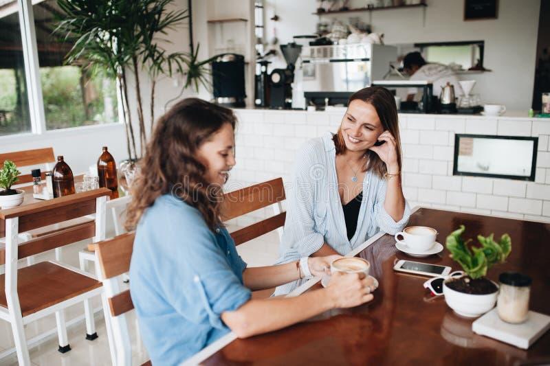 聊天在咖啡馆的愉快的女性朋友 说闲话和喝咖啡的两美丽的年轻女人 图库摄影