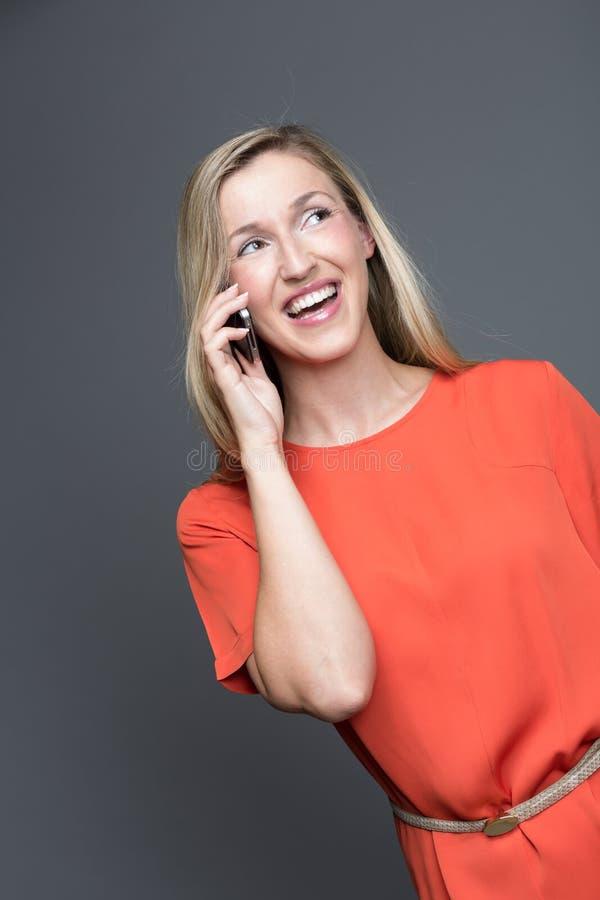 聊天在她的手机的笑的妇女 免版税图库摄影