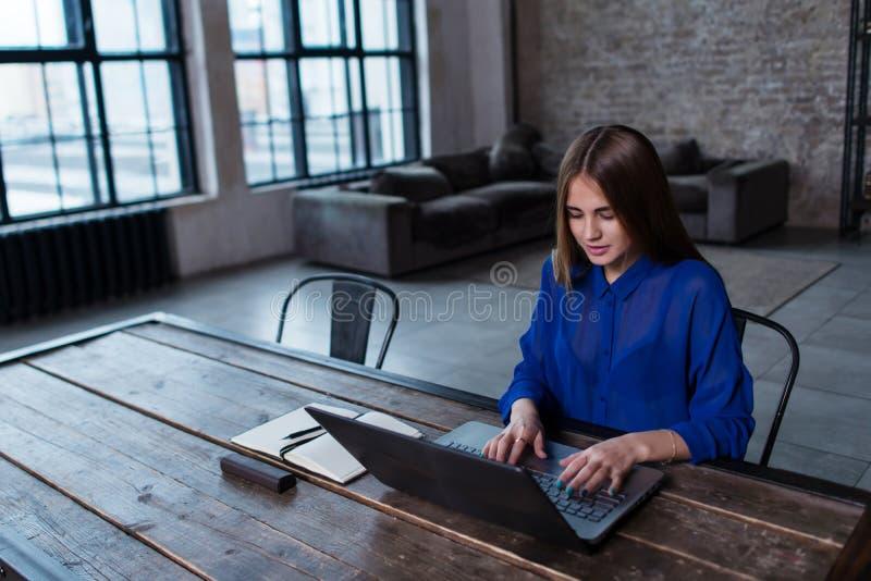 聊天在她的膝上型计算机的一个微笑的学生女孩的正面图 库存图片