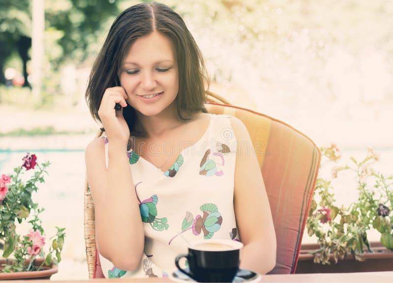 聊天在她的移动电话的妇女 图库摄影