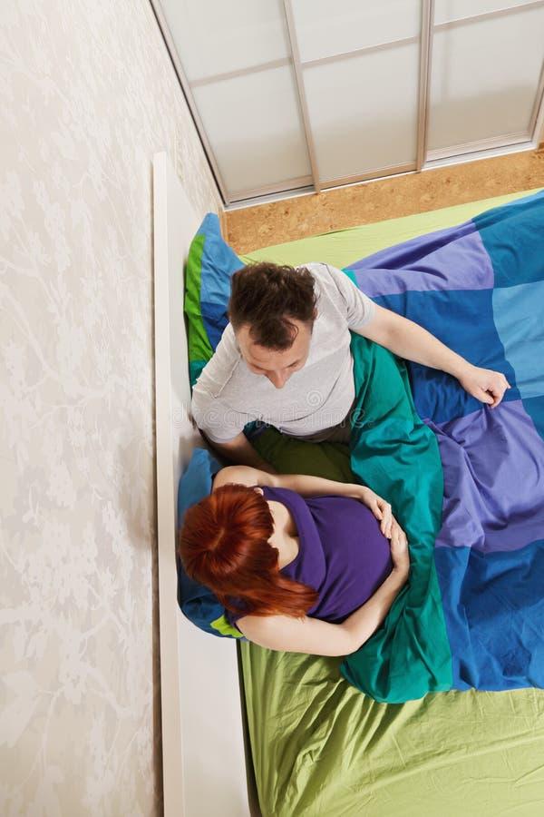 聊天在床上的夫妇在头顶上 库存图片