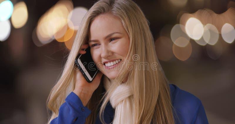 聊天在手扶的移动设备的迷人的年轻白肤金发的妇女 库存图片