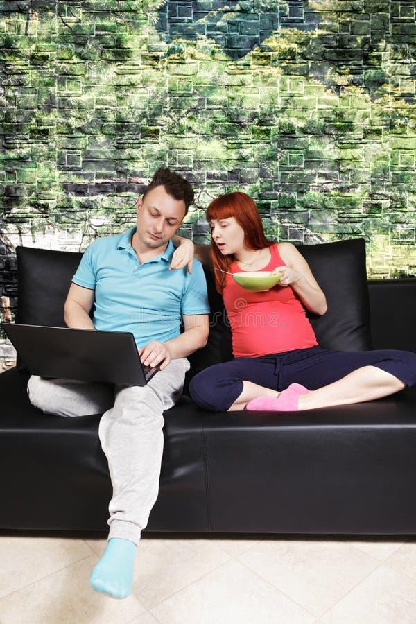 聊天在沙发的怀孕的夫妇 免版税库存照片