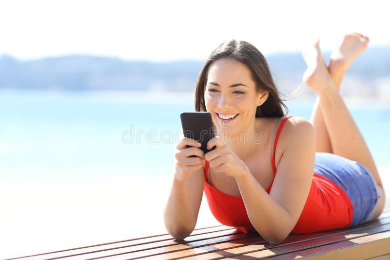 聊天在海滩的电话的愉快的妇女 免版税库存照片