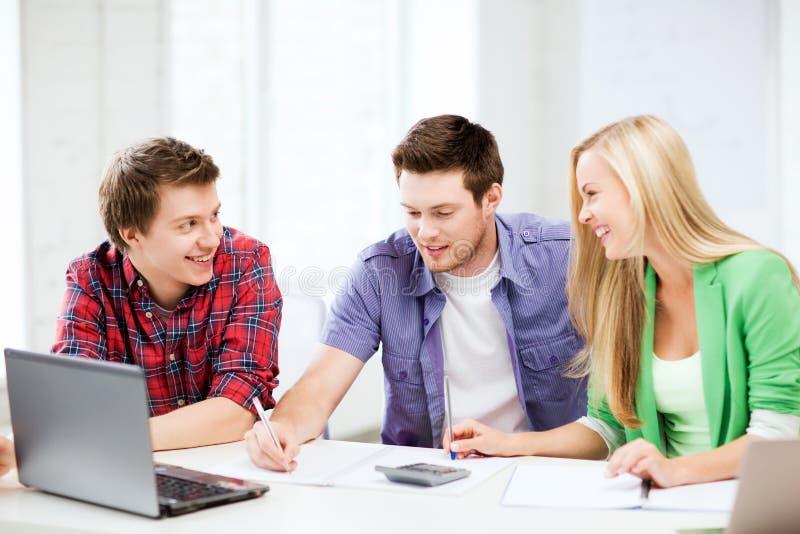 聊天在演讲的学生在学校 免版税库存图片