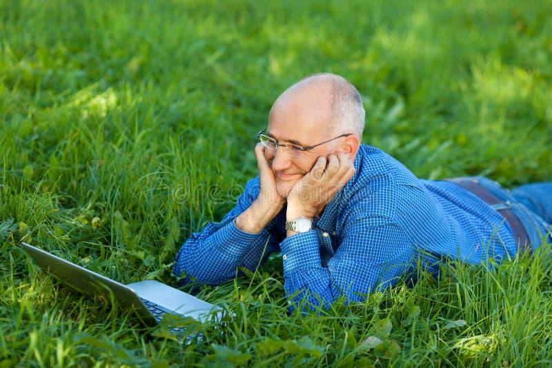 聊天在网上在膝上型计算机的商人,当说谎在草时 图库摄影