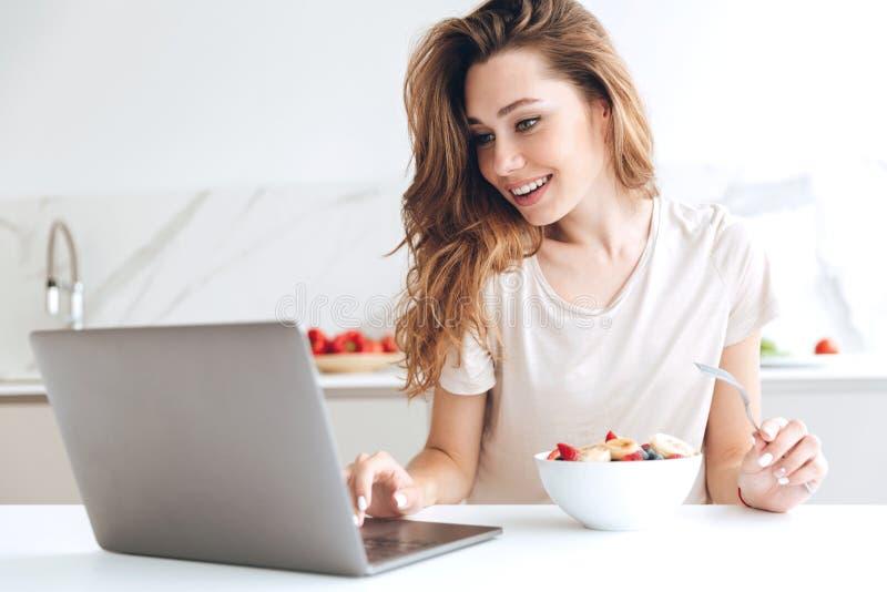 聊天在膝上型计算机和吃果子的俏丽的妇女 免版税库存图片