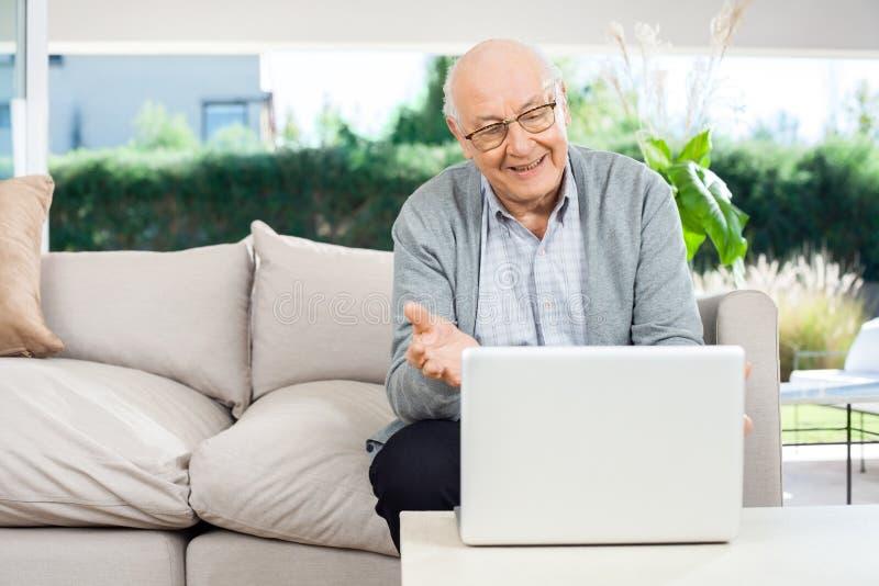 聊天在膝上型计算机的愉快的老人录影在门廊 图库摄影