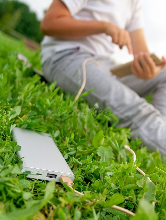 聊天在草坪的智能手机的男孩 库存照片