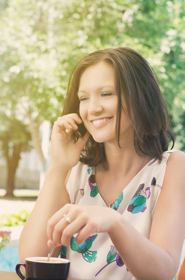 聊天在移动电话的可爱的妇女 图库摄影