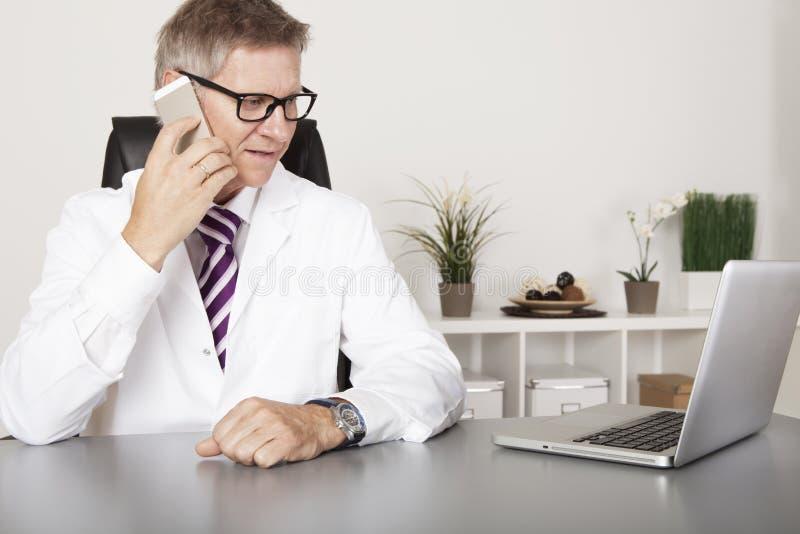 聊天在他的手机的医生 免版税库存图片