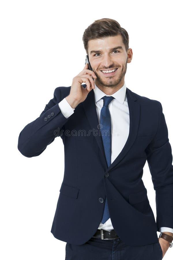 聊天在他的机动性的时髦的商人 图库摄影
