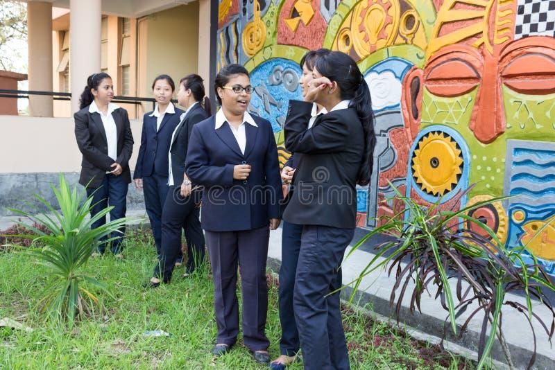 聊天愉快的女学生,校园 免版税库存图片