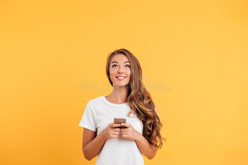聊天由手机的快乐的逗人喜爱的美丽的少妇 库存照片