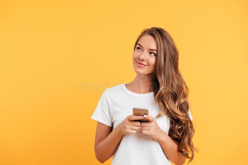 聊天由手机的快乐的逗人喜爱的美丽的少妇 免版税库存图片