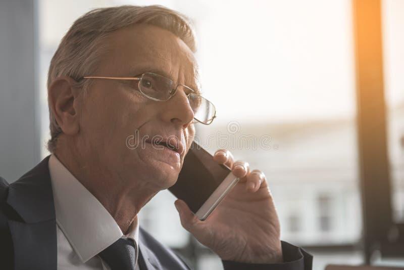 聊天由手机的被聚焦的资深商人 免版税库存图片