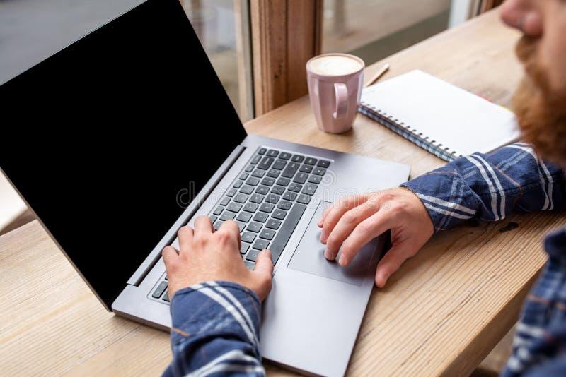 聊天通过网书的年轻人的播种的图象在咖啡店,坐在前面开放膝上型计算机的男性的工休期间 免版税图库摄影