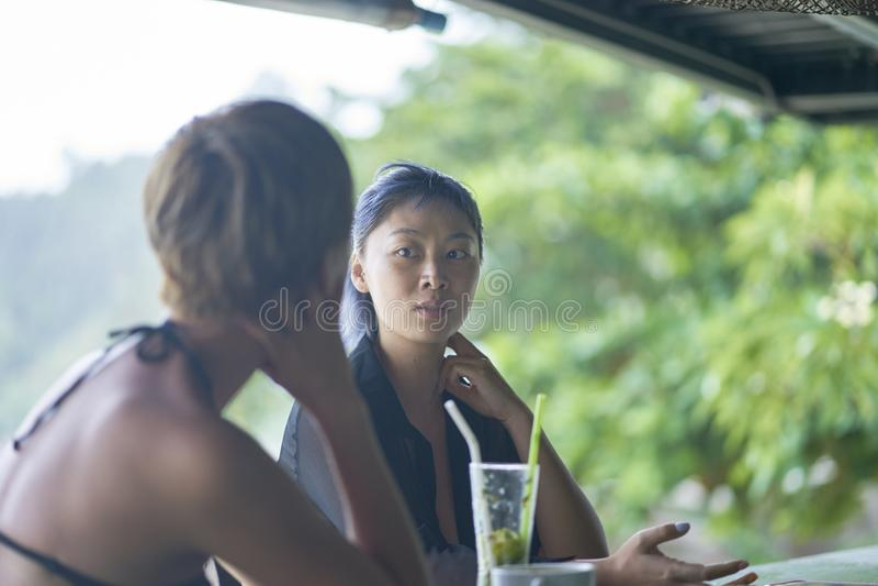 聊天,喝&微笑对海滩酒吧的2名亚裔妇女画象在夏天 免版税图库摄影