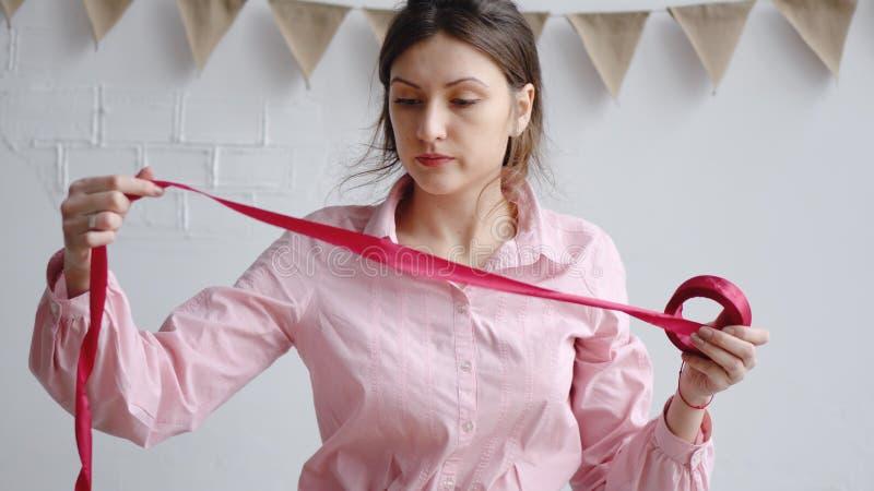 职业妇女卖花人解开红色丝带 库存照片