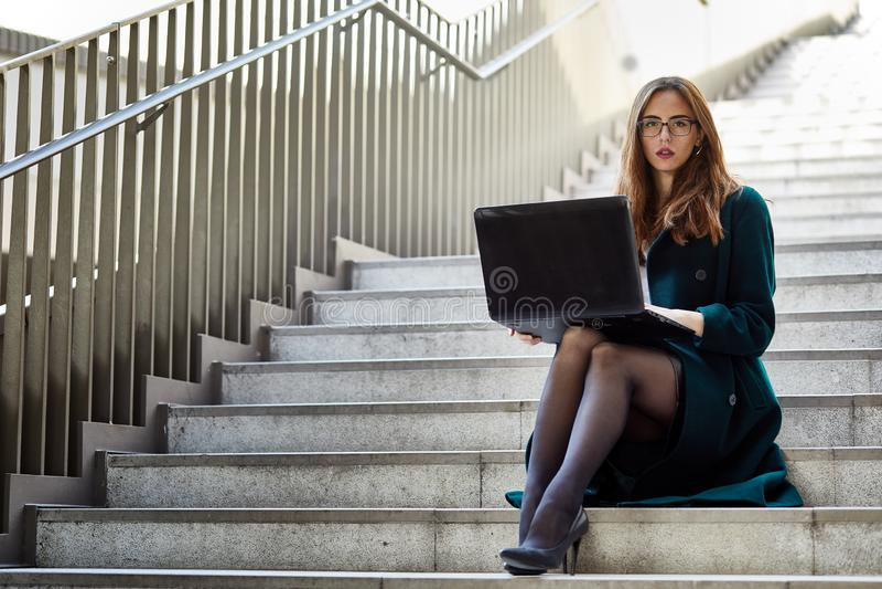 职业妇女戴着眼镜和坐在与一台膝上型计算机的一个楼梯在她的腿 库存照片