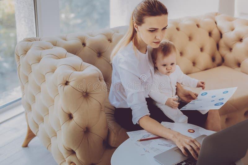 职业妇女键入的商业函件,当花费与一点女儿时的时间 免版税库存照片