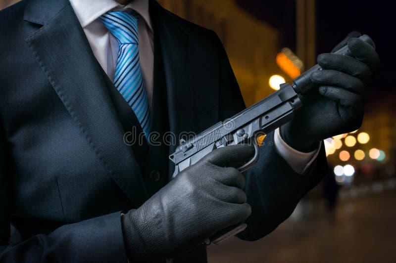 职业杀手或刺客拿着有遏声器的手枪在手上 免版税库存图片