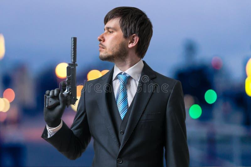 职业杀手或刺客拿着有遏声器的手枪手中在黄昏 免版税库存照片