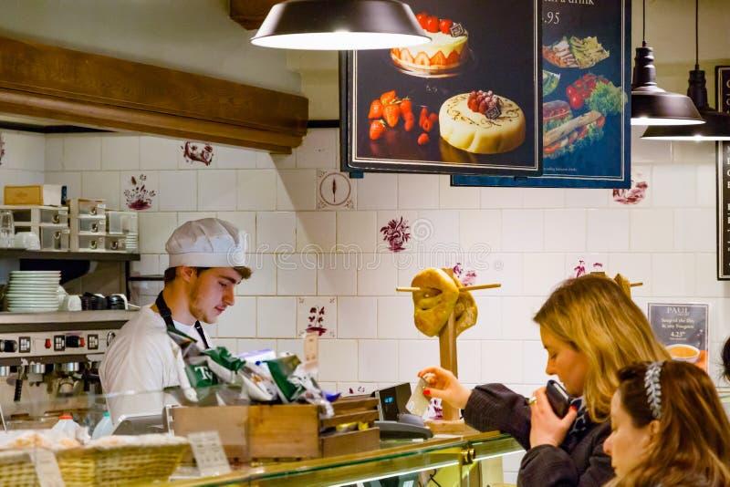 职员服务的顾客在保罗面包店商店在金丝雀码头 免版税库存照片