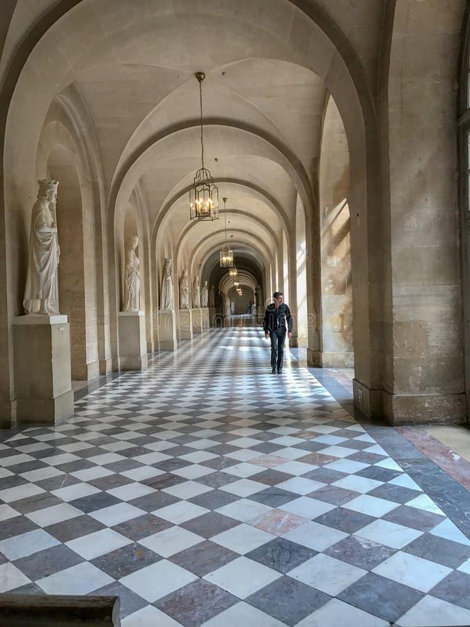 职员步行沿着向下长的被成拱形的走廊在凡尔赛宫 库存照片