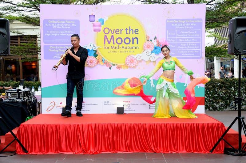 联合的萨克斯管和汉语跳舞在阶段的表现 免版税库存图片